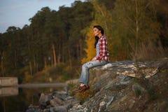 Frau, die auf Stein des Sonnenuntergangs und des Ozeans oder des Sees sitzt Lizenzfreie Stockfotografie