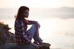 Frau, die auf Stein des Sonnenuntergangs und des Ozeans oder des Sees sitzt Lizenzfreies Stockfoto