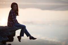 Frau, die auf Stein des Sonnenuntergangs und des Ozeans oder des Sees sitzt Stockfotografie