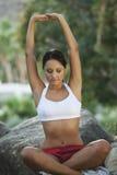 Frau, die auf Stein mit den Armen angehoben in Park meditiert Stockfotografie