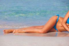 Frau, die auf Strand auf Sommerferien ein Sonnenbad nimmt stockbild