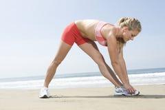 Frau, die auf Strand aufwärmt Lizenzfreies Stockbild