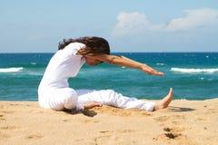 Frau, die auf Strand ausdehnt Stockfotos