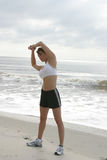 Frau, die auf Strand ausdehnt Lizenzfreie Stockfotografie
