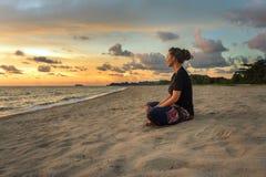 Frau, die auf Strand bei Sonnenuntergang sich entspannt Stockbild