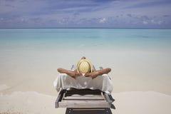 Frau, die auf Strand ein Sonnenbad nimmt Lizenzfreies Stockbild
