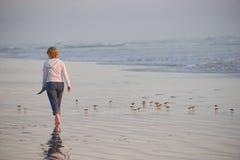 Frau, die auf Strand geht lizenzfreie stockbilder