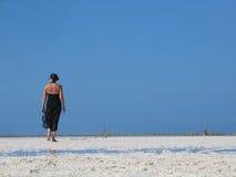 Frau, die auf Strand geht Stockbild