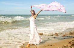 Frau, die auf Strand geht und Schal im Wind hält Stockfotografie