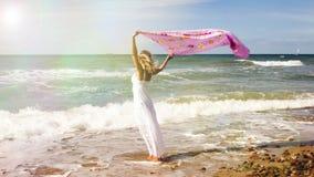 Frau, die auf Strand geht und Schal im Wind hält Lizenzfreie Stockfotos