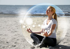 Frau, die auf Strand im Frieden meditiert Stockbild