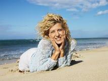 Frau, die auf Strand liegt Stockbild