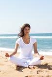 Frau, die auf Strand meditiert Lizenzfreie Stockbilder