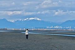 Frau, die auf Strand mit im Stadtzentrum gelegenem Vancouver und Mountain View geht Lizenzfreie Stockfotografie