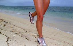 Frau, die auf Strand mit Seeküstenliniehintergrund läuft Stockbild