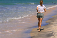 Frau, die auf Strand am Morgen läuft Lizenzfreie Stockfotografie
