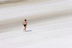 Frau, die auf Strand rüttelt Lizenzfreies Stockfoto