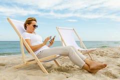 Frau, die auf Strand sich entspannt Stockfoto