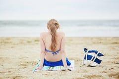 Frau, die auf Strand sich entspannt und ein Sonnenbad nimmt Stockfotografie