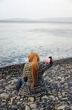 Frau, die auf Strand sitzt Lizenzfreies Stockbild