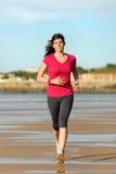 Frau, die auf Strand läuft Stockbild
