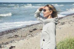 Frau, die auf Strand steht und den Abstand untersucht Stockfotos