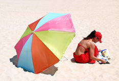 Frau, die auf Strandmesswert sitzt Stockbild