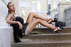 Frau, die auf Strichleiterjobsteps sitzt Stockfoto