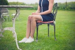 Frau, die auf Stuhl in einem Garten sich entspannt Stockfotografie