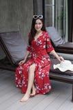 Frau, die auf Stuhl nahe Swimmingpool sitzt lizenzfreies stockfoto