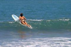 Frau, die auf Surfbrett sitzt Lizenzfreie Stockbilder