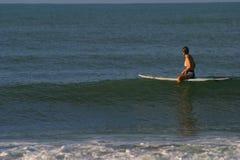 Frau, die auf Surfbrett sitzt Stockfotografie