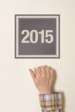 Frau, die auf Tür mit Nr. 2015 klopft Lizenzfreie Stockfotografie