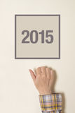 Frau, die auf Tür mit Nr. 2015 klopft Stockbild
