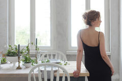 Frau, die auf Tabelle steht und sich lehnt Lizenzfreie Stockfotografie