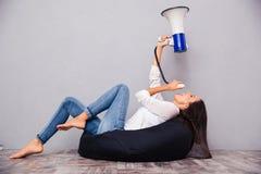Frau, die auf Taschenstuhl sitzt und im Megaphon schreit Stockbild