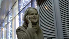 Frau, die auf Telefon und trinkendem Kaffee während spricht stock footage