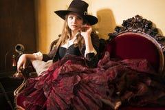 Frau, die auf teuren weichen Renaissancemöbeln faulenzt Lizenzfreie Stockfotografie