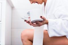 Frau, die auf Toilettenschreibenstextnachricht am Handy sitzt Lizenzfreies Stockfoto