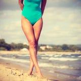 Frau, die auf tragenden Badeanzug des Strandes geht Stockfotos