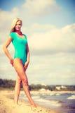 Frau, die auf tragenden Badeanzug des Strandes geht Lizenzfreie Stockfotos