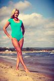 Frau, die auf tragenden Badeanzug des Strandes geht Lizenzfreie Stockfotografie