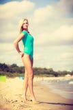 Frau, die auf tragenden Badeanzug des Strandes geht Lizenzfreie Stockbilder
