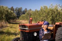 Frau, die auf Traktor beim Schreiben auf Klemmbrett sich lehnt Stockfotos