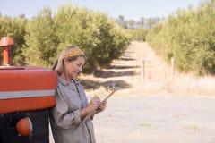Frau, die auf Traktor beim Schreiben auf Klemmbrett sich lehnt Lizenzfreie Stockbilder