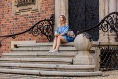 Frau, die auf Treppe des alten Haus- und Getränkkaffees sitzt stockbild