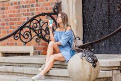 Frau, die auf Treppe des alten Haus- und Getränkkaffees sitzt lizenzfreie stockfotografie