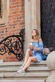 Frau, die auf Treppe des alten Haus- und Getränkkaffees sitzt stockfoto