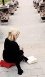 Frau, die auf Treppen sitzt und ein Buch liest Stockfotos