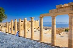 Frau, die auf Treppenhaus des Propylaea auf der Akropolise von sitzt Lizenzfreies Stockfoto